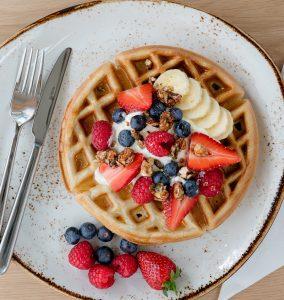 Freshly grilled waffle with berries, Greek yoghurt, honey and paleo granola