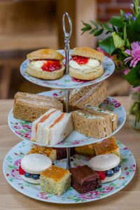A tasty selection of finger sandwiches, miniature cakes and scones with clotted cream and jam