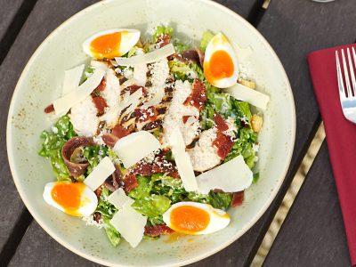Chicken Caesar salad with soft boiled egg, crispy pancetta, anchovies, herb croutons, gem lettuce, Caesar dressing