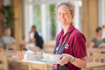 Volunteer serving teas and coffees