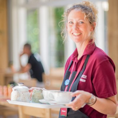 Volunteer working at The Grange serving tea and coffee